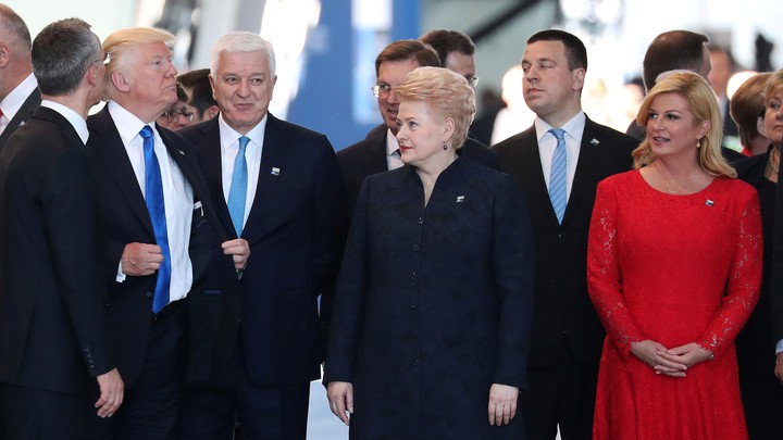Trump adjusts his jacket after pushing in front of Marković and other world leaders.