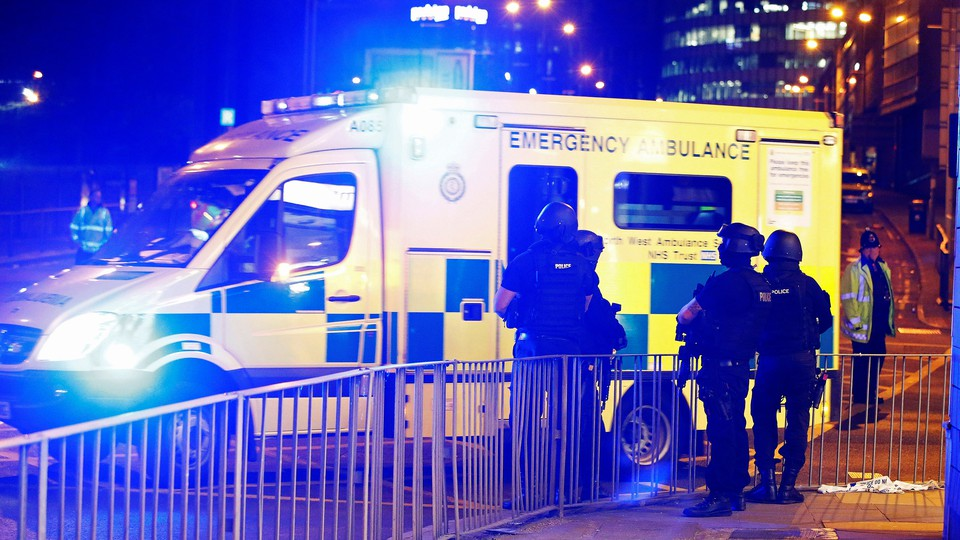 Armed police officers stand near the Manchester Arena.