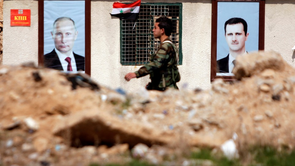 A Syrian government soldiers walks past rubble and posters of Bashar al-Assad and Vladimir Putin.