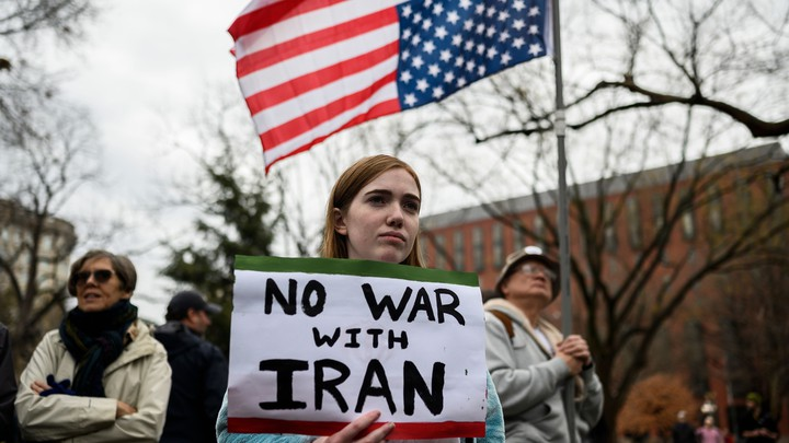 """A protester holds a sign reading """"No war with Iran."""""""