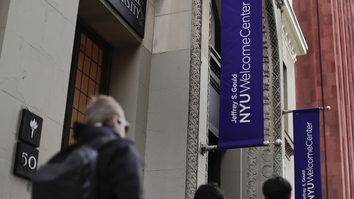Students walk along a street with NYU banners