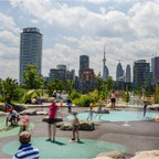 Families play in a splash park in Corktown Common, a green space near Toronto's waterfront that opened in 2014. New residential towers are being built in the area.