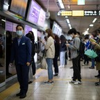 A Seoul Metro employee, second left, monitors passengers, to ensure face masks are worn, on a platform inside a subway station in Seoul, South Korea.