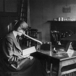 A woman sits reading a book while wearing a flu mask.