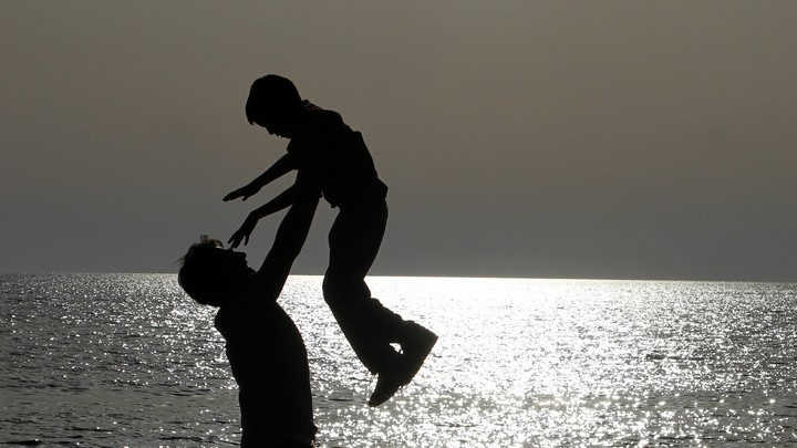 The silhouettes of a father and son playing on the beach