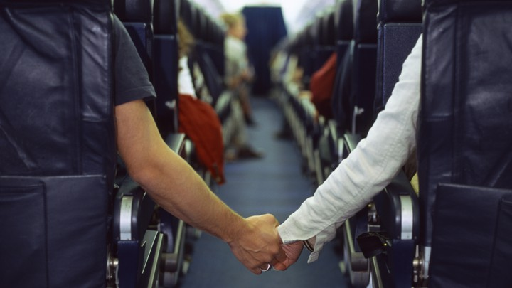 Two people hold hands across an airplane aisle