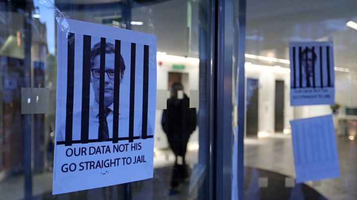 """Posters hang on a glass door depicting the Alexander Nix behind bars with the text, """"Our Data Not His. Go Straight to Jail."""""""