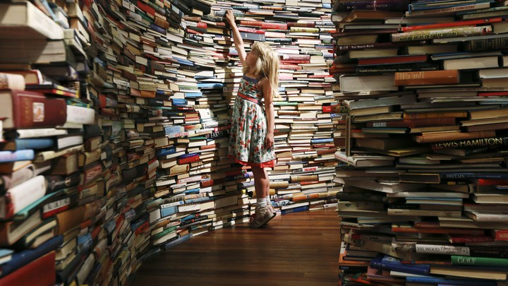 A young girl reaches for a book, surrounded by hundreds of other books.