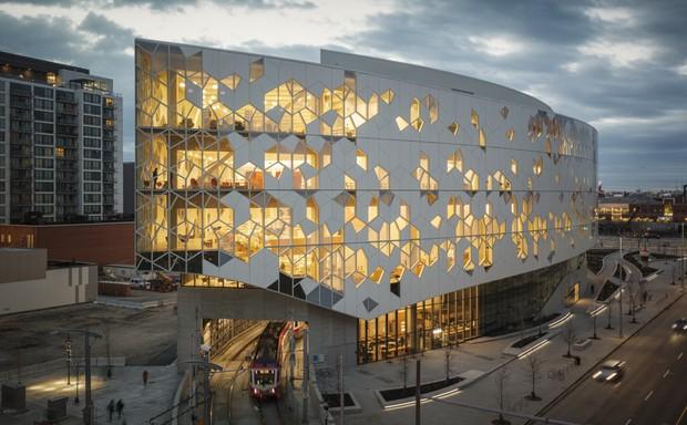 A light rail train pass through the new, Snøhetta-designed Calgary Central Library at dusk.