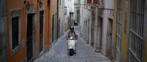 A man rides a scooter through a narrow, cobbled street lined by historic buildings.