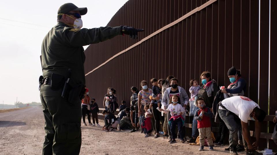 A Border Patrol agent and migrant families