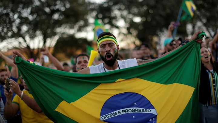 A protester holding a Brazilian flag