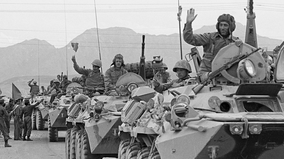A convoy of Soviet troops waves to crowds during its withdrawal from Afghanistan on May 15, 1988.