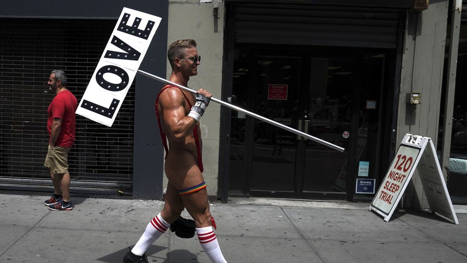 """A man in roller skates and an over-the-shoulder thong holding a sign that reads """"LOVE"""""""