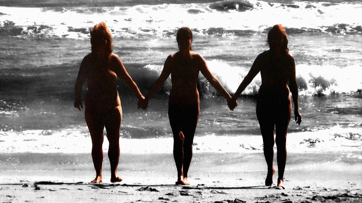 Three nude sisters hold hands on the beach.