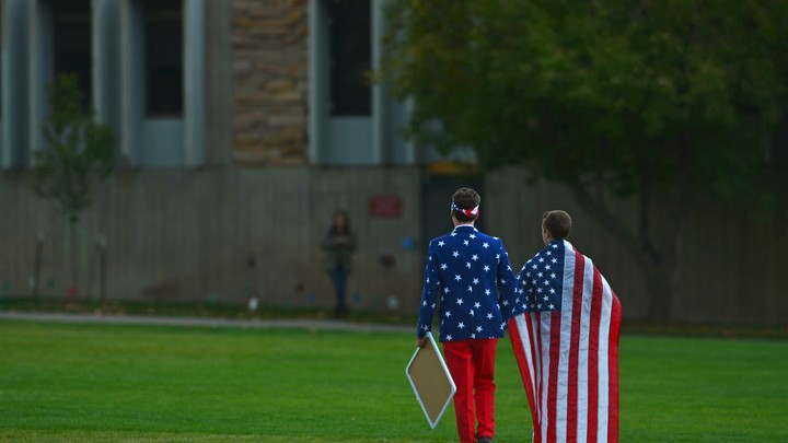 Two boys' backs face the camera. They are wearing American-flag apparel.