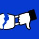 Facebook thumbs-up and thumbs-down logos, ripping apart a face mask.