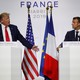 Donald Trump and Emmanuel Macron stand at lecterns as Trump delivers a speech.