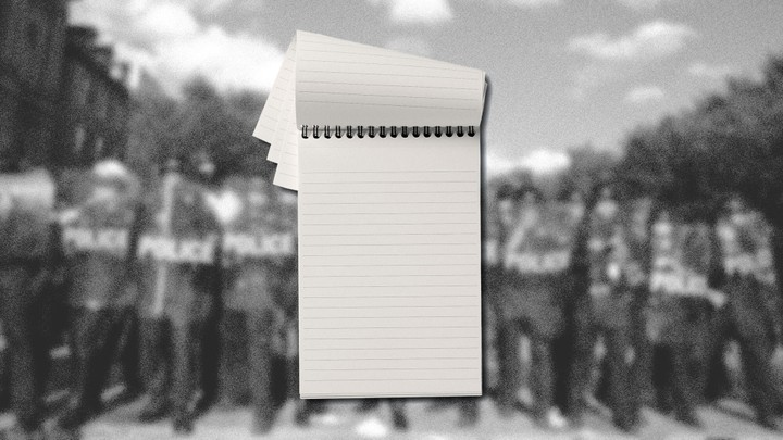 A pad of paper is set against a blurred image of police standing in a line with riot gear.