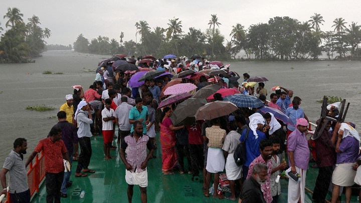 Volunteers stand under umbrellas on a boat that takes them to visit a flooded area in Kerala.