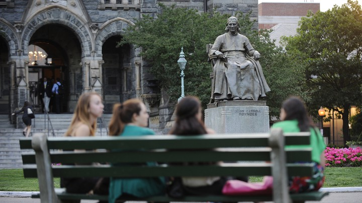 Students sit on a bench near Georgetown University's main lawn.