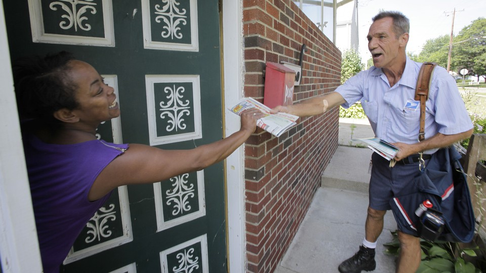A postal service employee delivering mail.