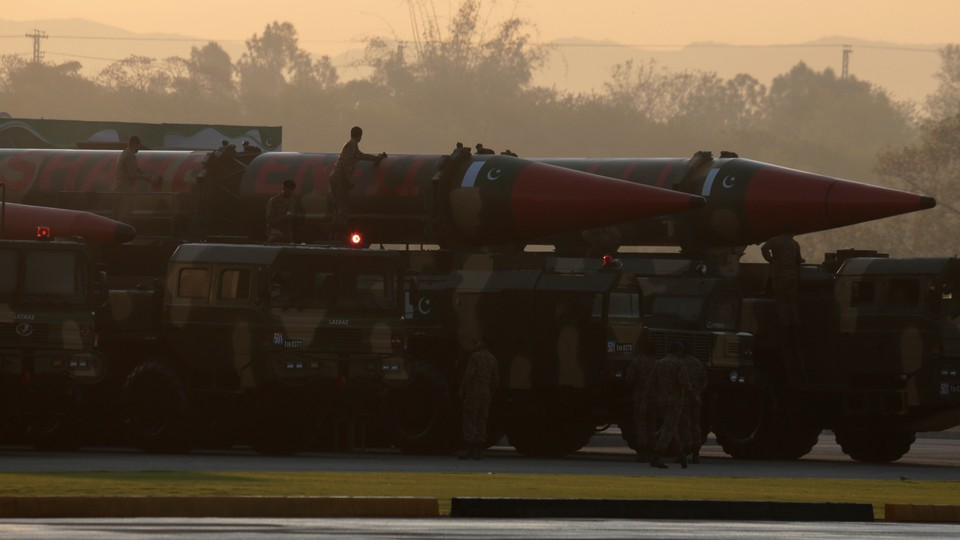 Workers cleaning missiles on transports