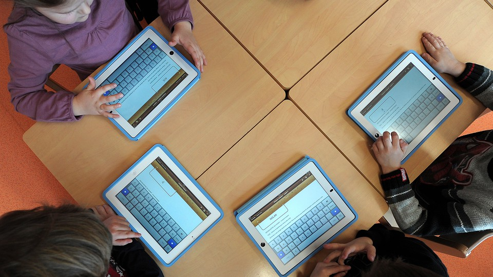 Children sit a table using tablet computers