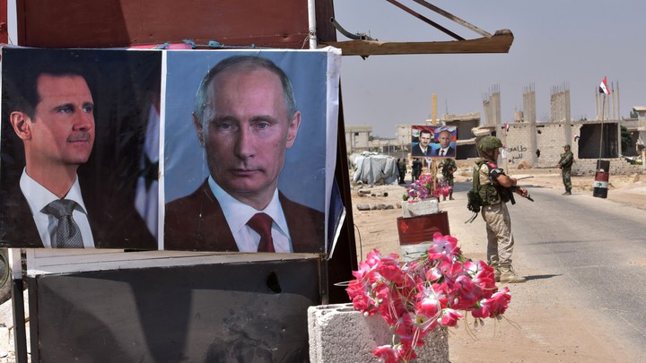 Flowers lie next to posters of Assad and Putin in Idlib.