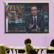 """A projector screen is filled with a screengrab from John Oliver's show. The word """"school"""" appears behind Oliver."""