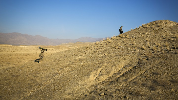 U.S. soldiers climb a hill in Afghanistan