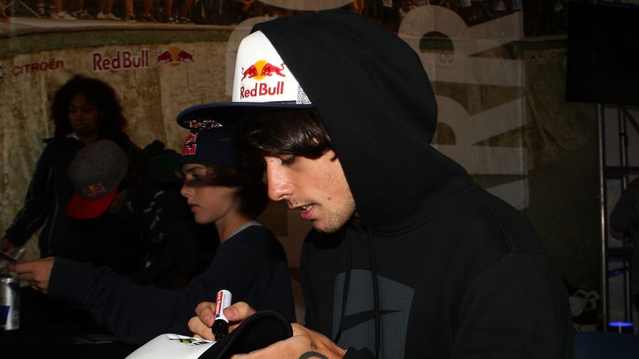 An X-Games athlete signs autographs at the event's Red Bull tent.