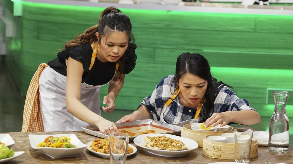 Ayesha Curry's 'Family Food Fight,' with Cat Cora and Graham Elliott, portrays cooking as a dynamic bonding ritual.