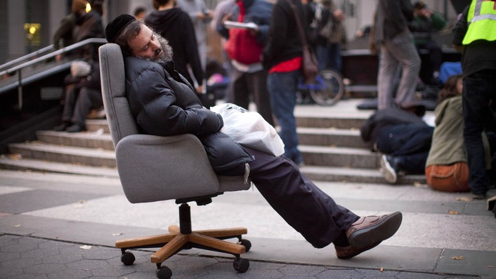 A protestor affiliated with the Occupy Wall Street movement falls asleep in an armchair in Foley Square in 2011.