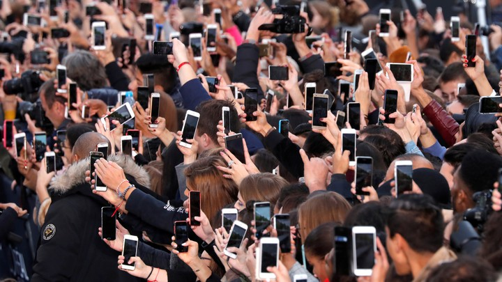 A crowd of people hold up their phones.