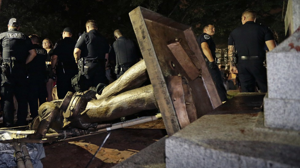 On Monday, August 20, 2018, police stand guard after the Confederate statue known as Silent Sam was toppled by protesters on campus at the University of North Carolina in Chapel Hill, North Carolina.