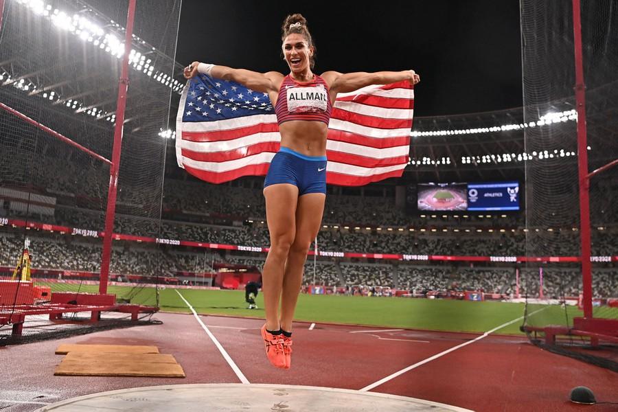 An athlete jumps on the field, celebrating, holding up an American flag as a cape.