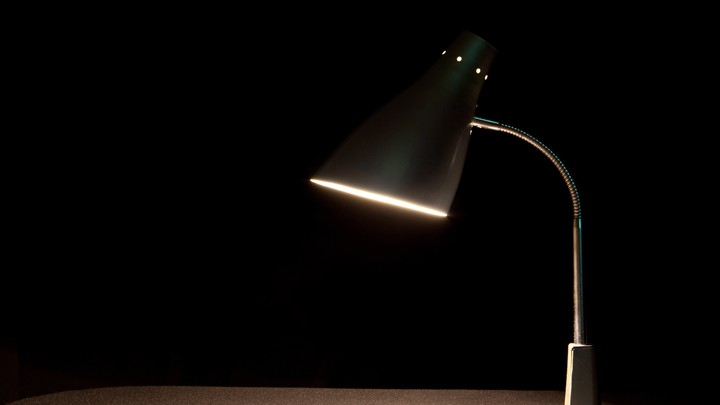 A lamp on a desk against a dark background