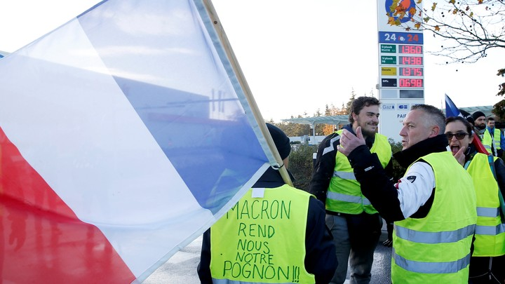 """Protesters wearing yellow vests, a symbol of a French drivers' block a gas station to protest against higher fuel prices, in Nantes, France, November 24, 2018. Inscription on the vest reads: """"Macron, give us back our money."""""""