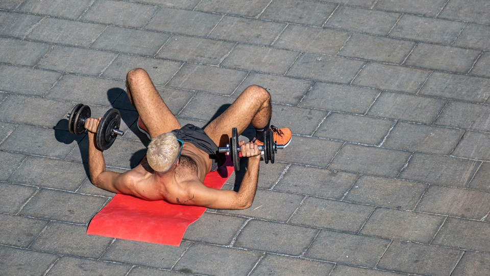 A shirtless man laying on a yoga mat and lifting weights.