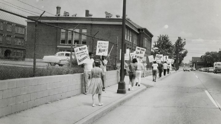Protestors carried signs asking for school redistricting and integration. They were on the sidewalk in front of IPS School 17 in the 1960s.
