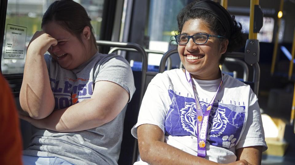 Two women smile on a public bus