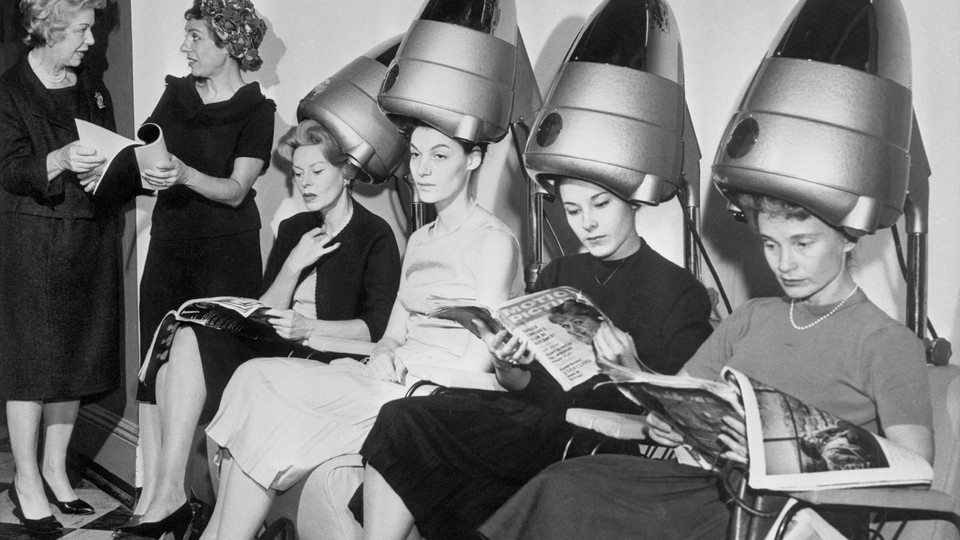 A group of women sit underneath hair dryers and read magazines at a hair salon.
