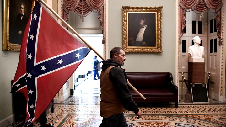 A Trump supporter carrying a Confederate flag through the U.S. Capitol.