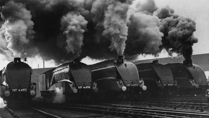 Five black steam engines blow smoke into the air.