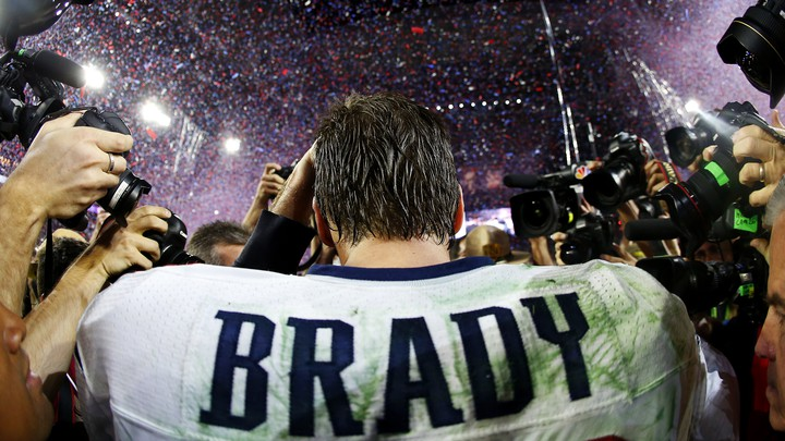 Tom Brady walks away from the camera in a football stadium, as a horde of photographers takes pictures of him.