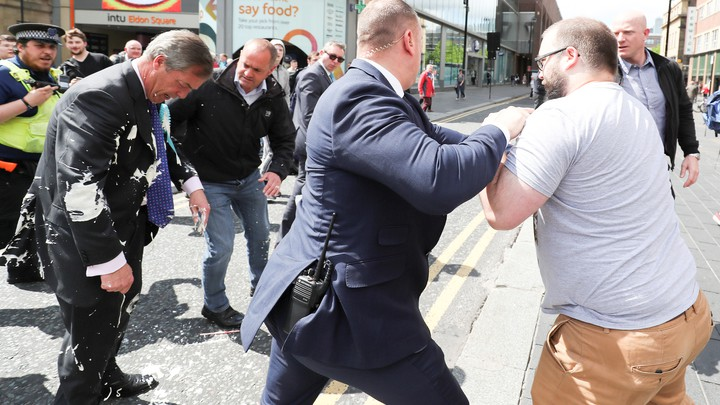 A security guard pushes back a man after he dumped a milkshake on Nigel Farage.