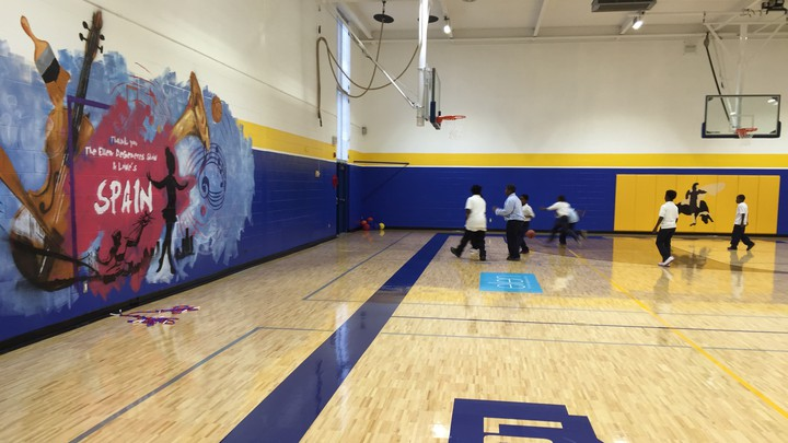 A group of children plays basketball on a brand new gymnasium floor. A mural with musical instruments and notes is pained with the school's name on the wall.