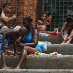 People apply sunscreen while sitting on the steps next to the Astoria Park Pool in New York.