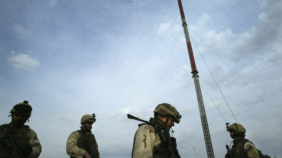 U.S. forces stand in front of Mosul TV-station transmitters.